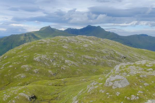 Photo of Ladhar Bheinn appearing dark in distance behind mound of Beinn Bhuidhe