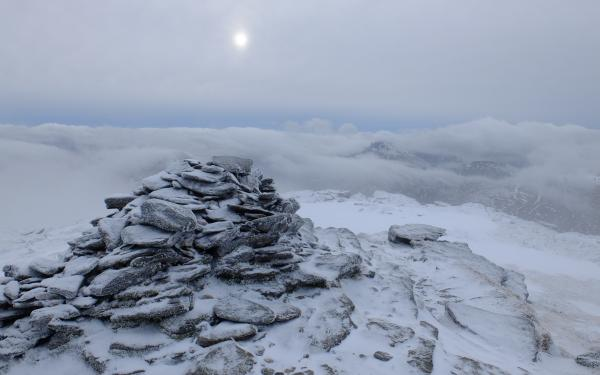 Photo of Summit of Beinn Dorain with low sun and low clouds behind